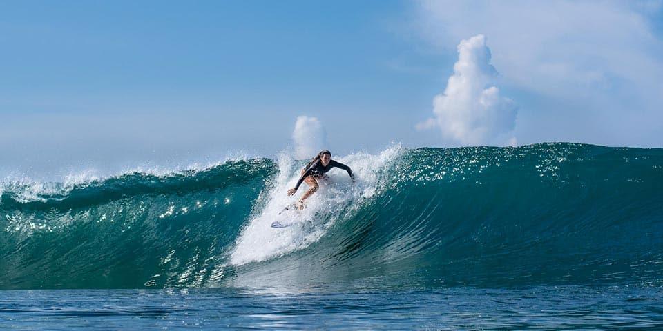Un surfero en una hermosa ola de color turquesa del mar de Cerdeña