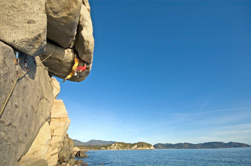Maurizio Oviglia scala a Villasimius una parete a strapiombo sl mare azzuro della Sardegna