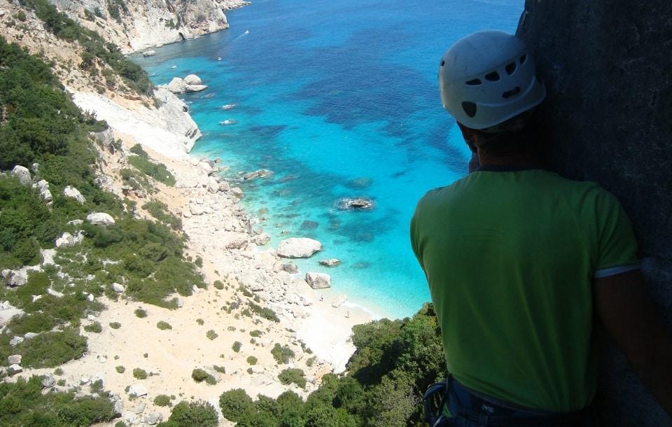Uno scalatore si affaccia dall'alto di una montagna sul mare trasparente della sardegna