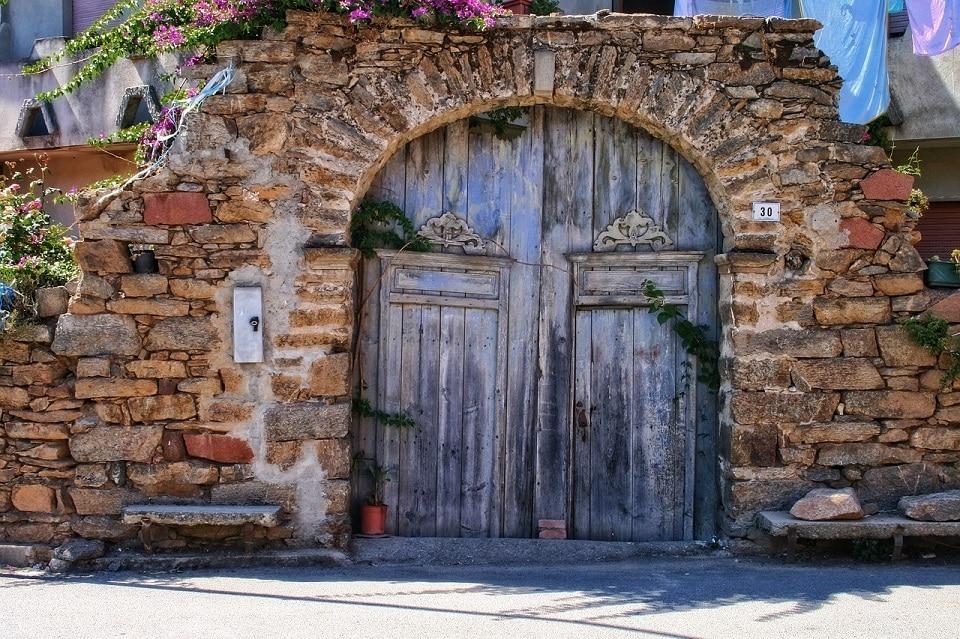 Il portone ad arco antico di una casa in pietra della Sardegna