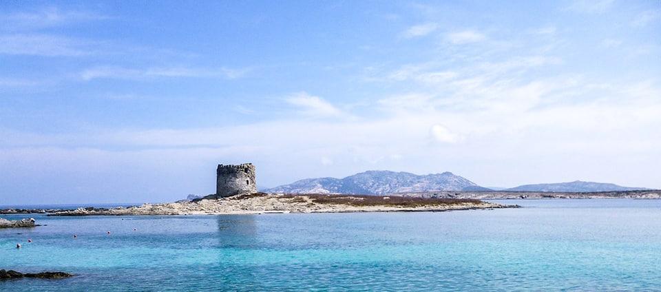 Das kristallklare Meer von La Pelosa mit seinem berühmten Turm und der Insel Asinara im Hintergrund